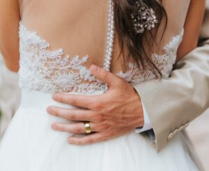 men's gold wedding band on groom with bride